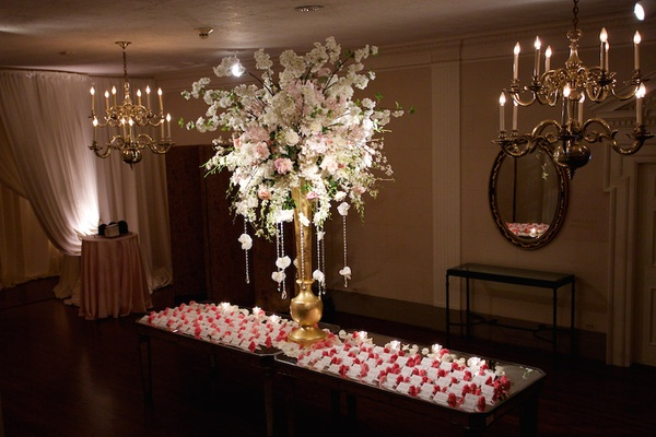 Wedding reception place card table with tall gold vase, white & pink flowers, cards with boutonniere