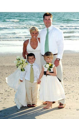 Bride and groom with flower girl and ring bearer on beach
