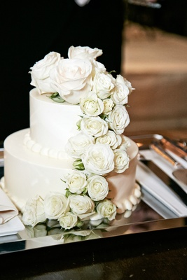 White wedding cake with white roses on a silver tray