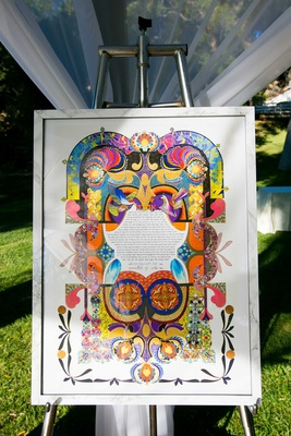 a brightly colored ketubah displayed at couples traditional jewish ceremony