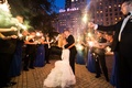 bride and groom in vera wang kiss surrounded by sparklers