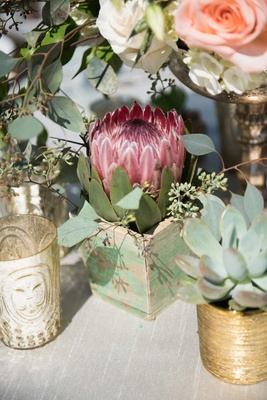 Garden wedding reception table with red protea, leaves in wood box, succulent in golden vessel