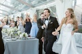 guests cheer as bride and groom enter tented wedding reception