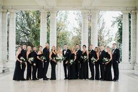 bride in berta wedding dress groom with bridesmaids in black evening gowns groomsmen in tuxedos