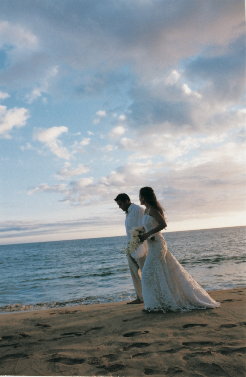 bride and groom walk across the sand next to the ocean