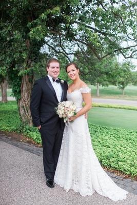 Bride in lace Legends Romona Keveza wedding dress with groom in tuxedo bow tie ivory blush bouquet