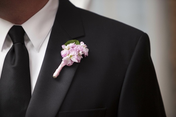 Groomsman boutonniere of small light pink flowers