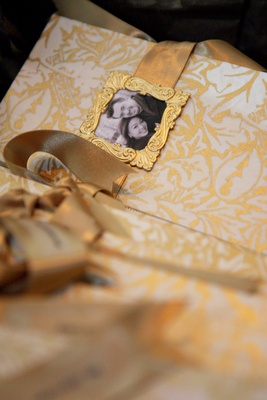 Gold wedding program with framed photo of couple