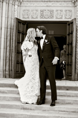 Black and white photo of bride and groom leaving church doors going down steps kiss after ceremony