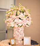 Welcome table at a Jewish wedding ceremony with vase covered in pale purple, orange, white roses