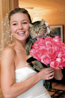 Bride holding bouquet and kitten with flower collar