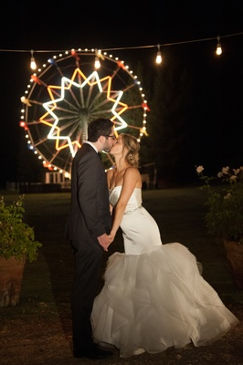 Bride and groom kissing in front of carnival ride