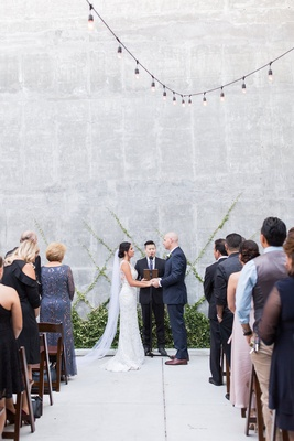 Wedding ceremony concrete no aisle runner greenery at altar on wall criss cross pattern string light