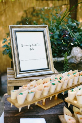 sweet and spicy cocktail nuts in bamboo cones in wooden stands with frame menu design outdoor weddin