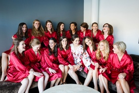 Bride in floral print robe and bridesmaids in red robes while getting ready bridal suite
