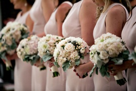 Bridemaids standing in line at church ceremony pink dresses pink and ivory bouquet flower