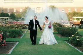 Bride and groom walk through garden with large fountain