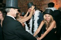 Wedding guests dancing in party hats and boas