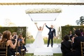 Guests taking photos with cell phones of bride and groom after ceremony holding hands raising them