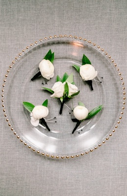 five boutonnieres with a single white flower and two green leaves on glass charger plate with gold t