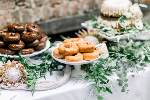 wedding dessert table with protea blooms, donuts, nothing bundt cakes