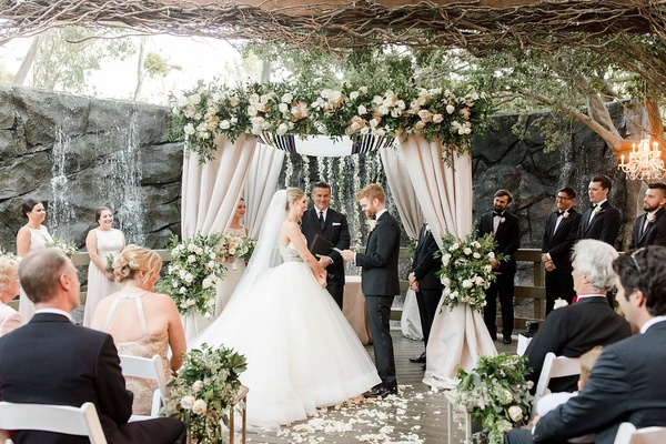 calamigos ranch wedding ceremony in front of waterfall, groom reads vows