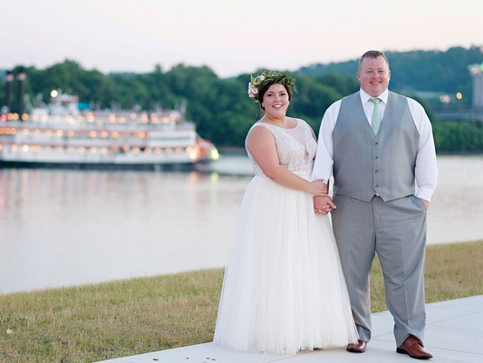 Bride in sleeveless wedding dress holding groom's hand by water river boat groom in grey vest