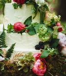 White wedding cake with hot pink peonies and greenery