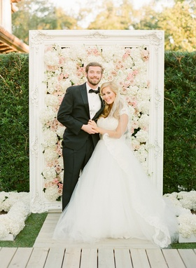 Bride in a Monique Lhuillier gown with a lace bodice and veil with groom in a black tuxedo