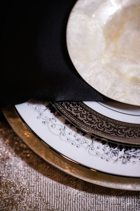 Wedding reception place setting with pearl charger, dessert plate, white china with party scene