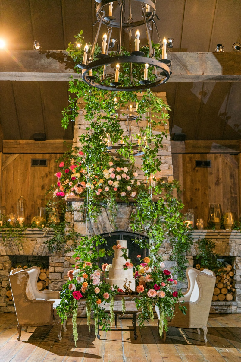 wedding reception stone fireplace greenery cake swing with flowers greens hovering off ground