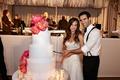 Bride and groom cutting white wedding cake