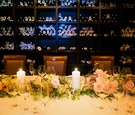 Small wedding reception in the wine cellar of Del Pasto with pastel pink, orange dahlias, roses