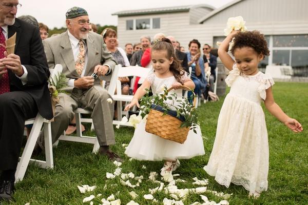 Flower girls tossing white flower petals short sleeve dresses grass aisle outdoor wedding