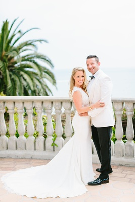 bride in fitted ines di santo wedding dress, groom in white tuxedo jacket and black pants