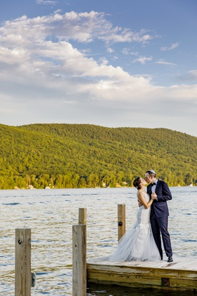 bride in custom hayley paige wedding dress, groom in navy tuxedo, newlyweds kiss on lake dock