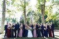 Outdoor wedding photo portrait wedding party bridesmaids pink mauve burgundy groomsmen in blue suits