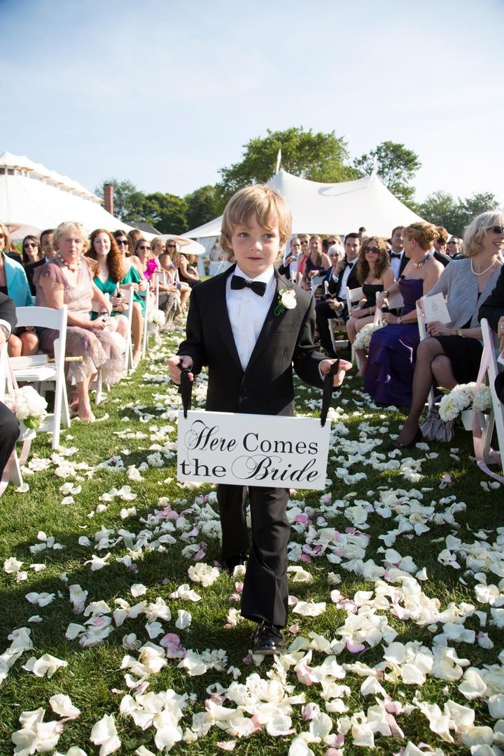 "Ring bearer holds ""Here Comes the Bride"" signage"
