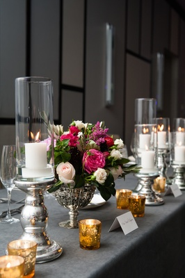 Silver linens and vases with gold votive candles