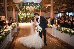 wedding ceremony wood floor bride in mermaid wedding dress flower petals tossed by guests neutral