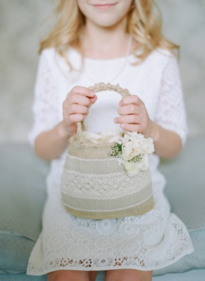 Flower girl holding basket made of burlap and lace with roses