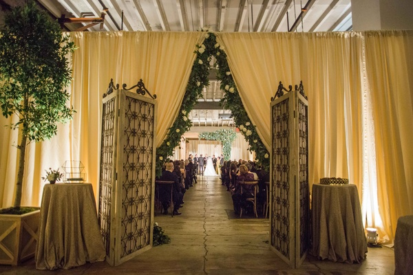 Indoor wedding ceremony with drapery eucalyptus garland trim doors to ceremony reception space