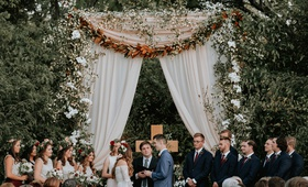 wedding ceremony outdoor tall arch greenery magnolia leaves cross drapery