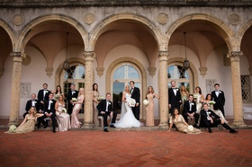 bride and groom with groomsmen in tuxedos, bridesmaids in gold, posed at museum cloisters