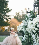 Flower girl in champagne tulle ball gown with basket and flower crown gates with white flowers