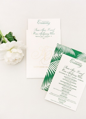 Wedding programs with green palm frond graphic in envelopes with golden monogram