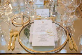 gold flateware, gold-rimmed charger plates, menu with ribbon and cream blossom