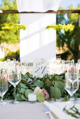 table number in gray calligraphy surrounded by foliage with blush flowers on white table linen