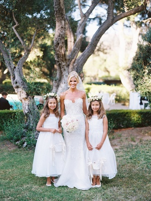 the bride standing with her young flower girls in matching white dresses and flower crowns baskets