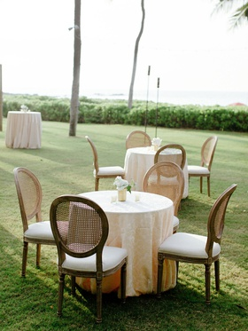outdoor wedding cocktail hour on grass lawn destination wedding hawaii wood cane back oval chairs